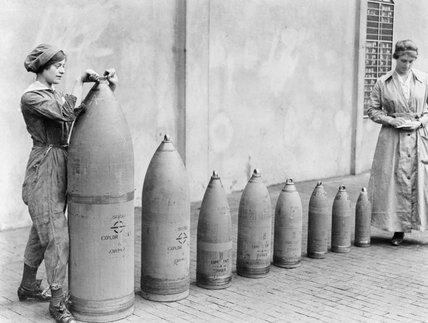 Two women munitions workers stand beside examples of the shells produced at National Shell Filling Factory No.6, Chillwell, Nottinghamshire during the First World War. Nicholls Horace © IWM (Q 30017)